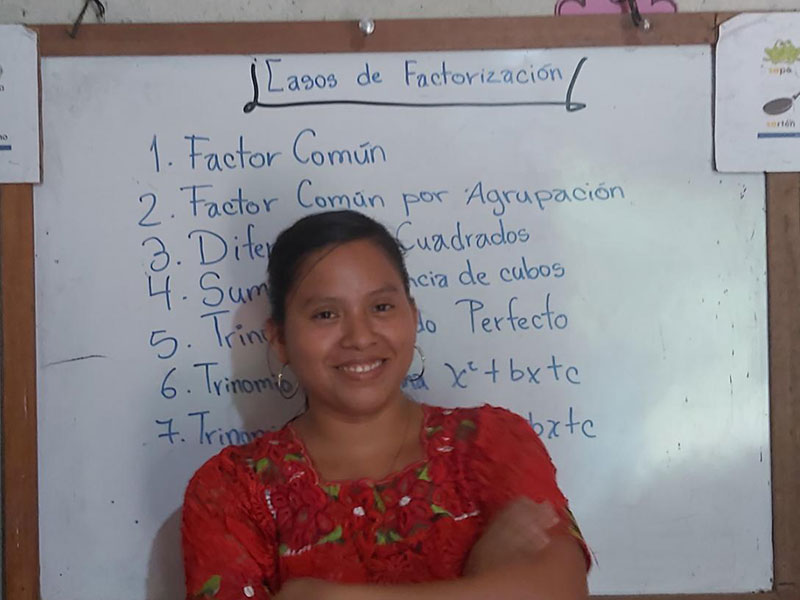 Photo of Guatemalan woman standing in from of a white board